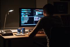 Back view of modern programmer sitting and writing code - stock photo