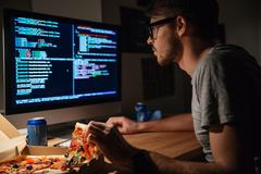 Concentrated software developer eating pizza and coding - stock photo