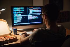 Back view of focused programmer writing code and eating pizza - stock photo