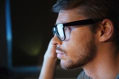 Thoughtful young man with bristle in glasses sitting and thinking - stock photo