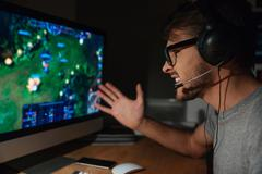 Cheerful gamer playing game on computer using headphones Stock Photos
