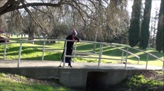 Old Lady With Cane Standing and Walking On Park bridge Stock Footage