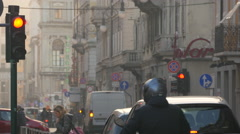 Cars and scooter stopping at the red light on a street in Trieste Stock Footage