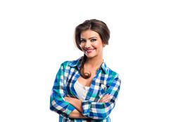 Woman with plait in blue and green checked shirt smiling - stock photo