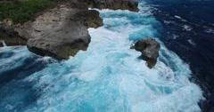 4K AERIAL OF DANGEROUS CHOPPY OCEAN WAVES CRASHING ON ROCK CLIFFS Stock Footage
