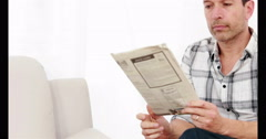 Smiling man reading newspaper while sitting on the couch Stock Footage