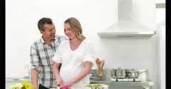 Pregnant woman making a salad with her husband Stock Footage