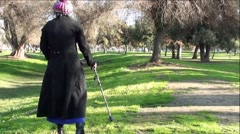 Old Woman In Black Trench Coat and Funny Hat Walking In Park - stock footage