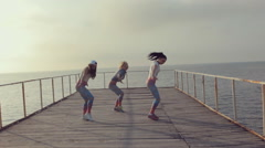 Girls in bright leggings professionally dancing modern dance on a wooden pier Stock Footage