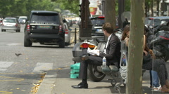 Man eating and women sitting on a bench on Avenue de la Grande Armee in Paris Stock Footage