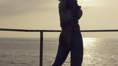 Sport woman dressed in leggings moves booty on the pier near the sea at a sunset Stock Footage