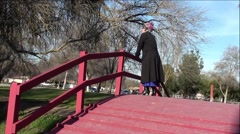 Old Women On Wooden Bridge Reaching Up At Trees - stock footage