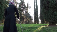 Old Woman with Cane Walking Up Hill in Beautiful Park - stock footage
