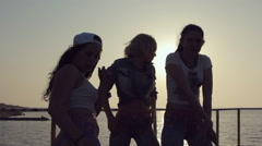 Three cheerful girls dressed in the same leggings dancing at sunset near the sea Stock Footage