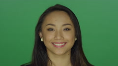 Beautiful young woman smiling, on a green screen studio background - stock footage
