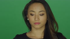 Beautiful young woman looking sad, on a green screen studio background - stock footage