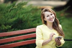 young beautiful  woman sitting on bench in a green park holding and using her - stock photo