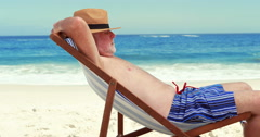 Senior man sleeping on deck chair Stock Footage