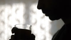 Silhouette of man, addicted alcoholic, drinking short drink at home - stock footage