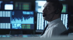 Stockbroker is talking on a headset while working on a computer in a dark office Stock Footage