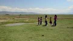 Group of girls, children play game on flat land, field, rural area, sunny day Stock Footage