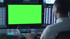 Man is working on a computer with mock-up green screen in a dark office - stock footage