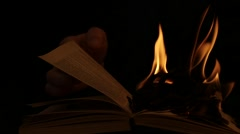 Hand turn pages of burning book dolly shot black background Stock Footage