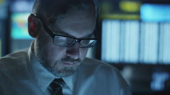 Manager is working on a computer in the evening in dark office with displays - stock footage
