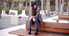 Fashionable young woman sitting waiting on a bench - stock footage