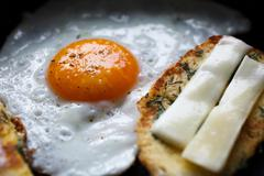 fried egg and bread with cheese on the pan - stock photo
