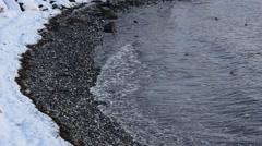 Cold waves splashing on snowy sea shore Stock Footage