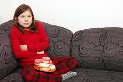 Little girl stomach ache because he ate a lot of donuts Stock Photos