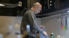 Bold man, cleaning kichen, drinking beer - stock footage
