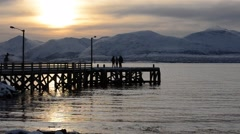 people wandering on pier at sunset with snowy mountain background - stock footage