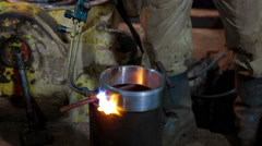 Human warms up the mold of metal by burner Stock Footage