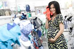 Happy young mother looking for baby clothes in a store. - stock photo