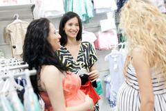 Lovely pregnant women looking for baby clothes in a store for their new babies. Stock Photos