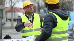 Gratitude between engineers with safety jackets and yellow hardhats. Outdoors Stock Footage