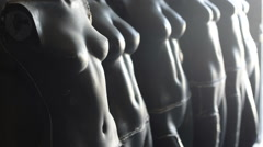 Armless nude female black mannequin bodies standing in workshop Stock Footage