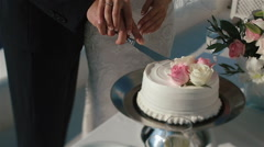 Happy fabulous couple cuts their wedding cake with holding hands - stock footage