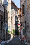 TOURRETTES-SUR-LOUP, FRANCE - OCTOBER 30, 2014: Narrow cobbled street with fl - stock photo