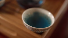 Man Takes the Porcelain Bowl with Thailand Blue Tea Stock Footage