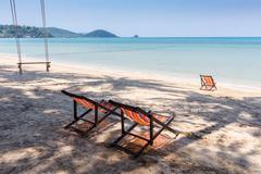 Stock Photo of Beach chairs on tropical sand beach.
