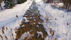 Flying low over tranquil stream blanketed in winter snow. Stock Footage