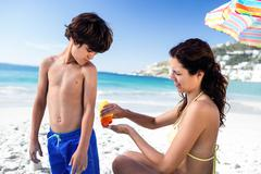 Cute mother applying sunscreen to her son on the beach - stock photo