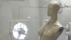 Painted armless female mannequin torso in paint shop, tilt shot Stock Footage