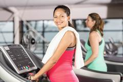 Smiling pregnant woman using treadmill at the leisure center Stock Photos