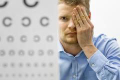 Eyesight check. male patient under eye vision examination Stock Photos