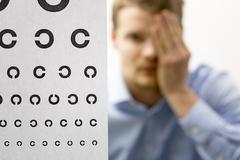 Eyesight check. male patient under eye vision examination. focus on test char Stock Photos