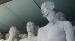 Group of unfinished naked male mannequins standing, warehouse, pan Stock Footage